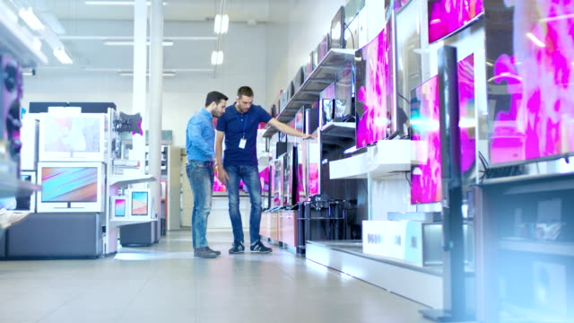 In the Electronics Store Professional Consultant Shows Latest 4K UHD TV's to a Young Man, They Talk about Specifications and What Model is Best for Young Man's Home. Store is Bright, Modern and Has all the Latest Models. In the Electronics Store Professional Consultant Shows Latest 4K UHD TV's to a Young Man, They Talk about Specifications and What Model is Best for Young Man's Home. Store is Bright, Modern and Has all the Latest Models. electrical equipment stock videos & royalty-free footage