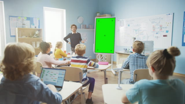 In the Elementary School Classroom: Teacher Uses Vertical Green Mock-up Screen Interactive Digital Whiteboard to Explain Lesson to Diverse Group of Schoolchildren. Multi Ethnic Kids Learning Science In the Elementary School Classroom: Teacher Uses Vertical Green Mock-up Screen Interactive Digital Whiteboard to Explain Lesson to Diverse Group of Schoolchildren. Multi Ethnic Kids Learning Science middle school teacher stock videos & royalty-free footage