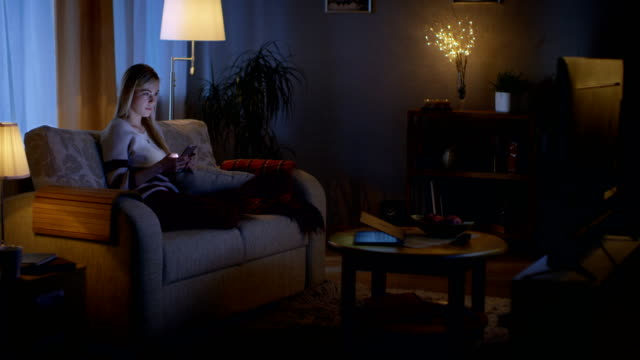 In the Evening Beautiful Young Woman Relaxes on a Couch in Her Cozy Living Room. She Uses Her Smartphone and Simultaneously Watches TV. In the Evening Beautiful Young Woman Relaxes on a Couch in Her Cozy Living Room. She Uses Her Smartphone and Simultaneously Watches TV. Shot on RED EPIC-W 8K Helium Cinema Camera. watching tv stock videos & royalty-free footage