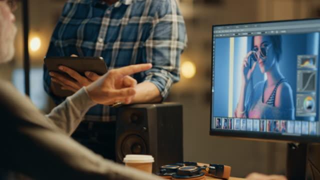 夕方のクリエイティブ中年のフォトエディタでは、デスクトップコンピュータ上で動作し、画像編集ソフトウェアを使用して、タブレットコンピュータを使用する若い専門家との会話を持っ� - 編集者点の映像素材/bロール