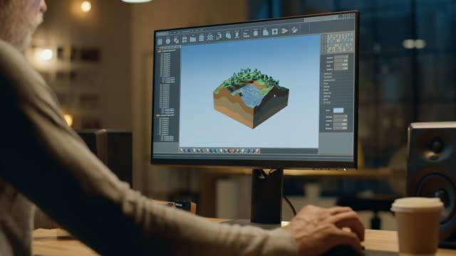 la sera lo sviluppatore creativo di videogiochi di mezza età lavora su un computer desktop con screen 3d videogame level design. elegante ufficio creative studio. colpo sopra la spalla - designer professionista video stock e b–roll