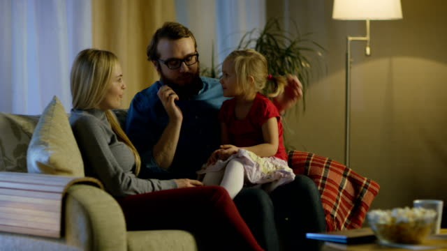 In the Evening Family Spends Time Together Sitting on a Couch in a Living Room. Little Girl Sits on Her Father's Laps and Parents Tickle Her. video