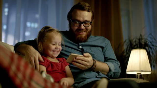 vídeos y material grabado en eventos de stock de en el padre de la tarde y la pequeña hija sentada en un sofá en la sala de estar ver videos divertidos en el teléfono inteligente. - madre e hijos