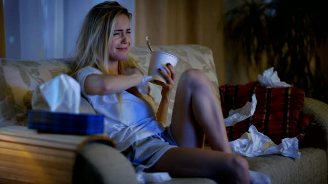 In the Evening Heartbroken Girl Sitting on a Sofa, Crying, Using Tissues, Eating Ice Cream and Watching Drama on TV. Her Room is in Mess. video