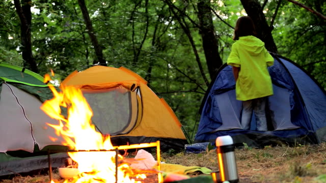 In the evening in the forest, children in a tent near the fire are going to spend the night video