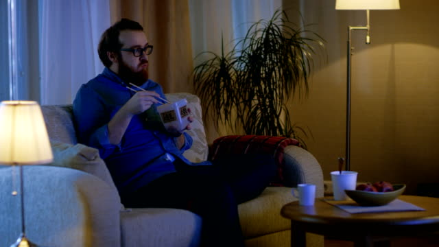 In the Evening Man Sitting on a Couch In His Living Room. He's Eating Asian Food from the Food Container and Watching TV Show. – Video