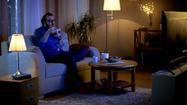 In den Abend Mann sitzt auf einer Couch In seinem Wohnzimmer. Er ist asiatische Essen aus dem Lebensmittel-Container und TV-Show zu beobachten. – Video