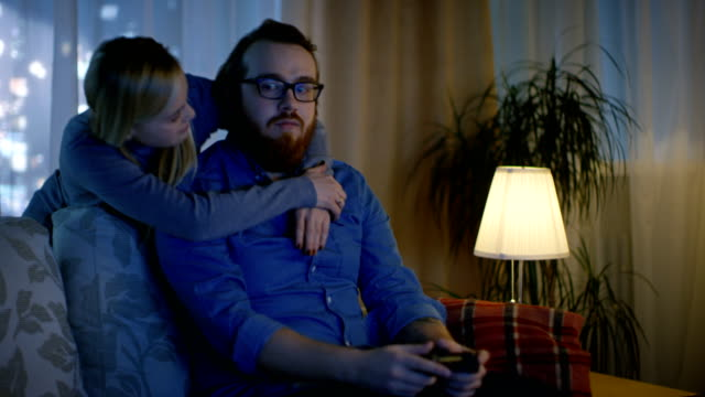 vídeos de stock e filmes b-roll de in the evening man sitting on a sofa playing videogames, his spouse comes in and hugs him. - man joystick