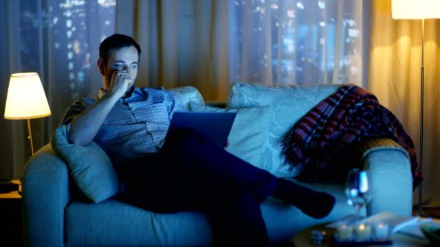 In den Abend Mitte im Alter Mann sitzt auf einem Sofa hält Laptop auf seine Knie und arbeiten auf It.TV eingeschaltet ist und es leuchtet Him.Skyscrapers sind aus dem Fenster gesehen. – Video