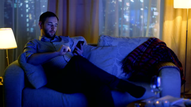 In the Evening Middle Aged Man Sits on a Sofa Uses Smartphone. Turned On TV Illuminates Him. In the Background Windows View of a Big City with Skyscrapers. video