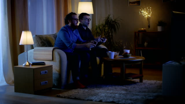 In the Evening Two Friends are Sitting on a Sofa in the Living Room and  Playing Competitive Video Games. One of Them Wins and He is Enjoying His Success. - vídeo