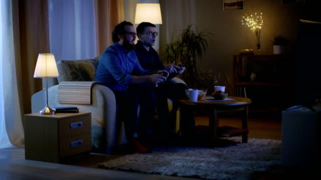 vídeos y material grabado en eventos de stock de en la noche dos amigos están sentados en un sofá en la sala de estar y jugando juegos de video competitivos. uno de ellos gana y está disfrutando de su éxito. - solteros jóvenes