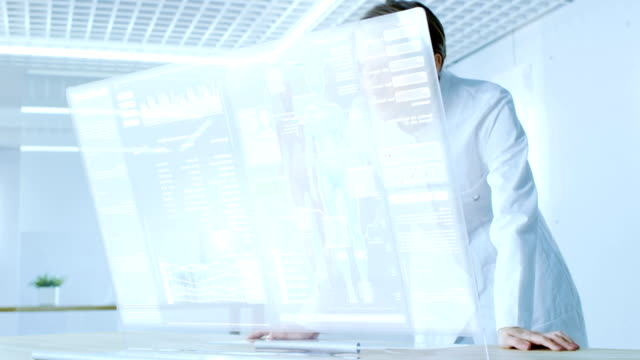 未来の実験室女性科学者作業の透明なコンピューターのディスプレイ上で人間の寿命を延長させようとします。画面には、様々 な人間の関連インフォ グラフィックやデータが表示されます。 - タッチスクリーン点の映像素材/bロール