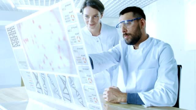 未来の実験室でオスとメスの科学者は透明表示するコンピューターに取り組んでいる話します。画面は、ヒト DNA のシーケンスを示しています。 ビデオ
