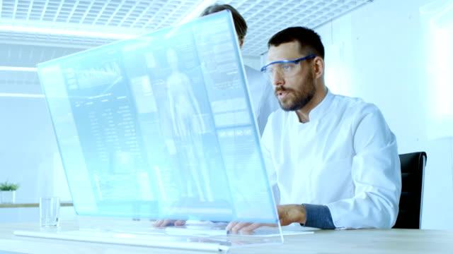 vidéos et rushes de dans le laboratoire futuriste mâles et femelles scientifiques au travail sur écran d'ordinateur transparents, ils tentent de prolonger la vie humaine. écran présente les différentes données et humain infographie connexes. - pratique médicale
