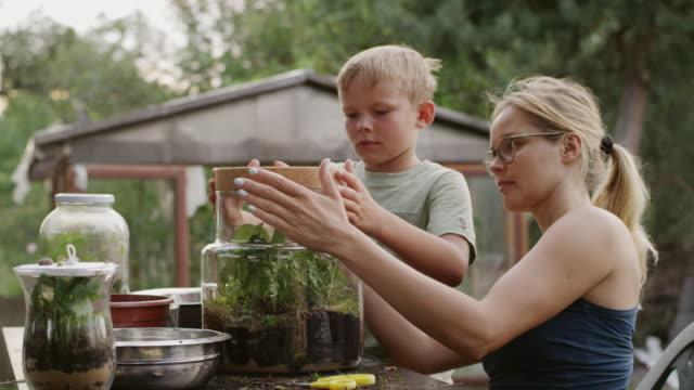 BRICOLAGE dans le jardin. Mère et fils - Vidéo