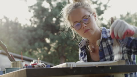 DIY in the garden Young woman working on diy project. Renovating old wooden crate craft stock videos & royalty-free footage