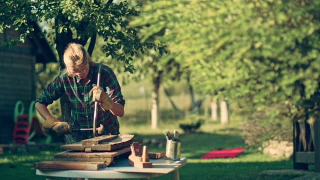 DIY in the garden. Woman renovating old wooden furniture video