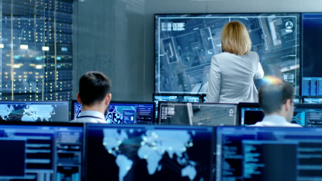 In the Government Surveillance Facility Team of Officers Organize Interception Plan with Help of Satellite Navigation. Big Screen Shows Top Down Images of the Target. video