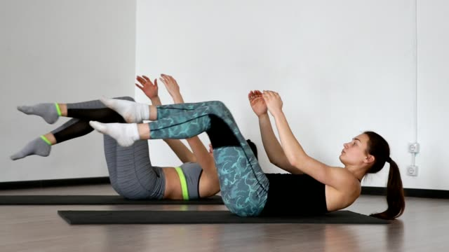 in the gym during the pilates exercise lying on the gym mats two girls lying on their back alternately pull their knees to the chest stretching the muscles of the thighs. synchronous execution of the exercise - metodo pilates video stock e b–roll