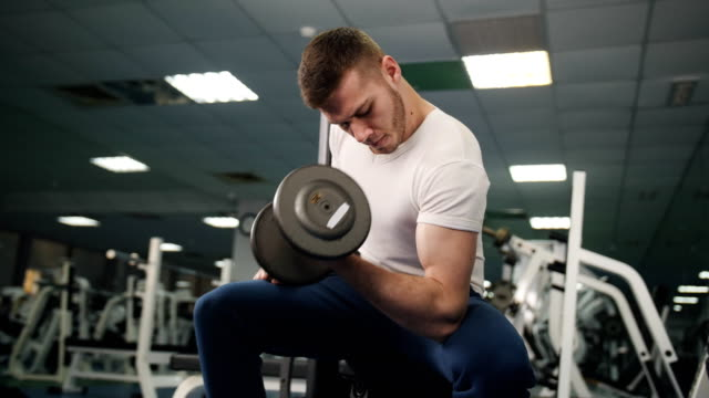 In the gym man sits and lifts a dumbbell with one hand. Young bodybuilder performs exercises on biceps with help of a heavy weight at counter with sports equipment.