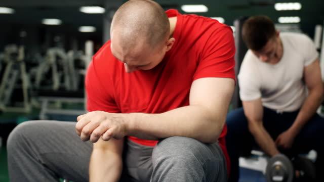 in der turnhalle sitzt der mensch und hebt mit einer hand eine hantel. der junge bodybuilder führt übungen auf bizeps mit hilfe eines schweren gewichts an der theke mit sportgeräten durch. - hantel stock-videos und b-roll-filmmaterial