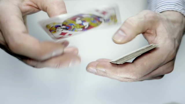 In the hands are a deck of cards, and the dealer deals cards to the players