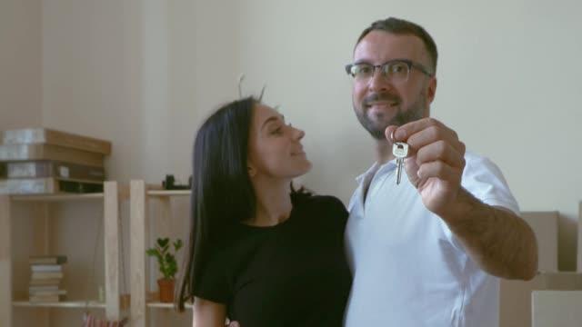 stockvideo's en b-roll-footage met in de handen van de echtgenoot bezit de sleutels naar het nieuwe appartement en zijn vrouw te kussen op de achtergrond van de planken met dingen. een man in bril en een wit t-shirt knuffels zijn dark-haired vrouw, die hem hugs - wit t shirt