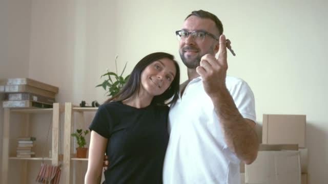 stockvideo's en b-roll-footage met in de handen van de echtgenoot bezit de sleutels naar het nieuwe appartement op de wijsvinger en zijn vrouw te kussen op de achtergrond van de planken met dingen. een man in bril en een wit t-shirt knuffels zijn dark-haired vrouw, die hem hugs - wit t shirt