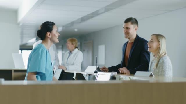 En el Hospital a la enfermera de recepción en deber respuestas emergencia llamada, después de que le dice joven que médico espera él. - vídeo