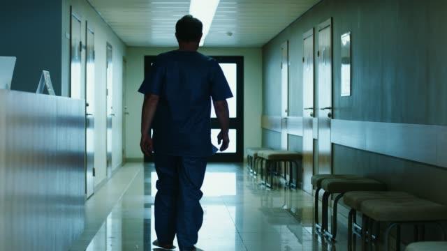 vidéos et rushes de dans l'hôpital vieillard pose des questions à la réception et des promenades puis dans le couloir. nettoyer les installations médicales modernes. - couloir