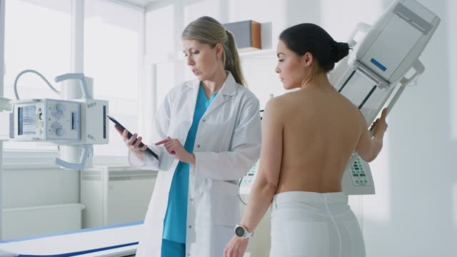 In the Hospital, Female Patient Listens to Mammography Technologist / Doctor Uses Tablet Computer, Explains Importance of Breast Cancer Prevention. Mammography Procedure. In the Hospital, Female Patient Listens to Mammography Technologist / Doctor Uses Tablet Computer, Explains Importance of Breast Cancer Prevention. Mammography Procedure. Shot on RED EPIC-W 8K Helium Cinema Camera. mammogram stock videos & royalty-free footage