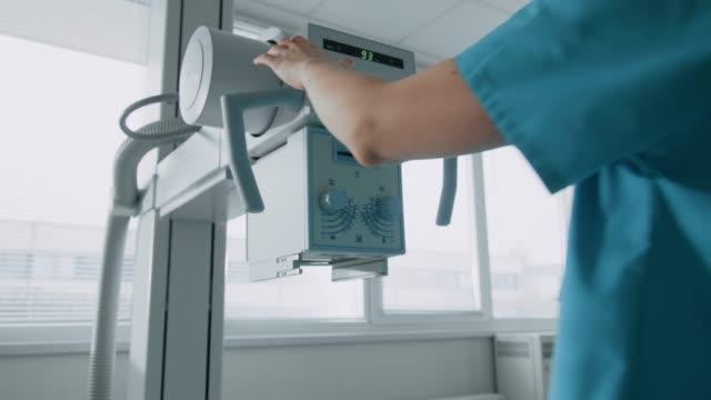 stockvideo's en b-roll-footage met in het ziekenhuis, vrouwelijke technicus past x-ray scanner / machine. modern ziekenhuis met technologisch geavanceerde medische apparatuur en professioneel personeel. - medische röntgenfoto