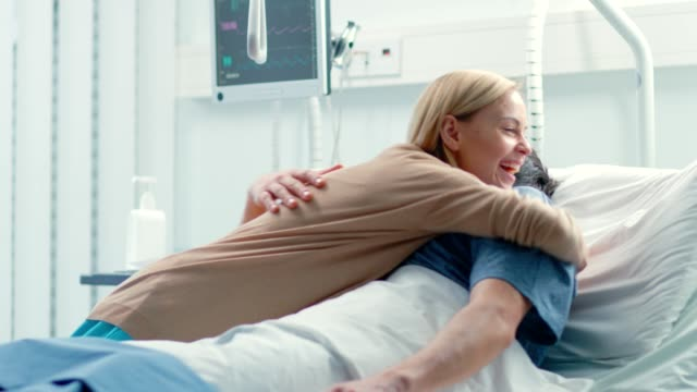 in the hospital, happy wife visits her recovering husband who is lying on the bed. they lovingly embrace and smile. - hospital stock videos & royalty-free footage