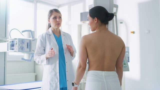 stockvideo's en b-roll-footage met in het ziekenhuis, mammography technoloog / arts past mammogram machine voor een vrouwelijke patiënt. vriendelijke dokter legt belang van screening op borst kanker preventie. technologisch geavanceerde moderne kliniek met professionele artsen. - breast cancer