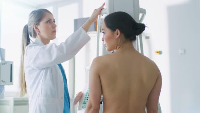 stockvideo's en b-roll-footage met in het ziekenhuis, mammography technoloog / arts past mammogram machine voor een vrouwelijke patiënt. technologisch geavanceerde moderne kliniek met professionele artsen. screening op borst kanker preventie. - breast cancer