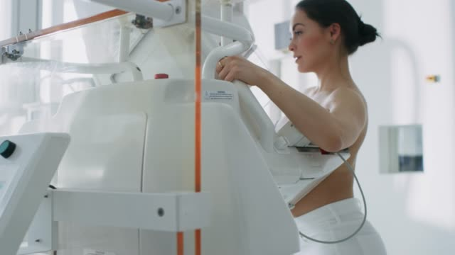 in the hospital, mammography technologist / doctor pushes button on mammogram machine activating female patient scan. friendly doctor explains importance of breast cancer prevention screening. modern technologically advanced clinic. - rentgen filmów i materiałów b-roll