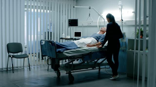 in dem krankenhaus mann im bett liegend während tochter sorgen und wartet, wenn er aufwachen werde. time passing zeitraffer-effekt. - krankenstation stock-videos und b-roll-filmmaterial