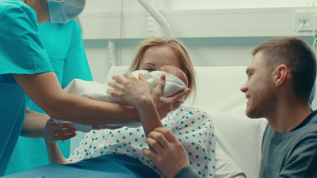 in the hospital midwife gives newborn baby to a mother to hold, supportive father lovingly hugging baby and wife. happy family in the modern delivery ward. - narodziny filmów i materiałów b-roll