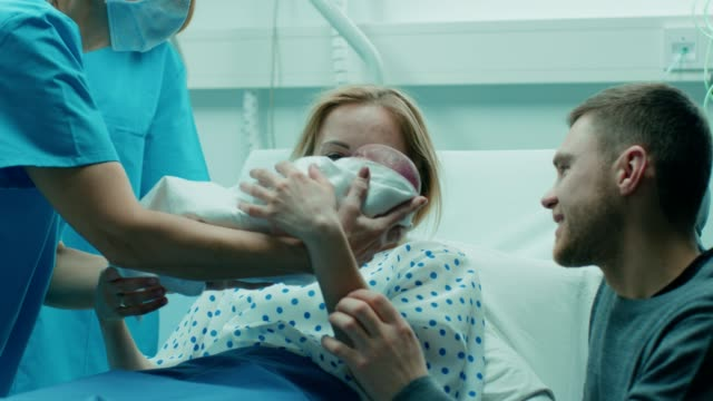 in the hospital midwife gives newborn baby to a mother to hold, supportive father lovingly hugging baby and wife. happy family in the modern delivery ward. - genitori video stock e b–roll