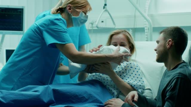 vidéos et rushes de dans l'hôpital sage-femme donne nouveau-né d'une mère de cale, soutien père embrasse amoureusement bébé et femme. héhé dans le quartier moderne de livraison. - naissance