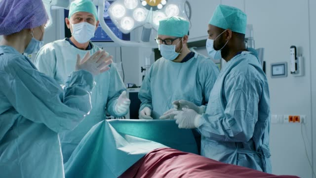 In the Hospital Operating Room Diverse Team of Professional Surgeons and Assistants Expect Finished Surgery and Applaud Successful Results. Professional Doctors Celebrating Successfully Saved Life. video