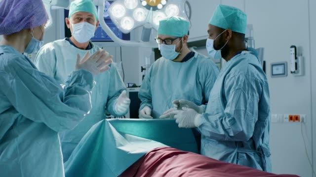 En el quirófano del Hospital equipo diverso de profesionales cirujanos y asistentes esperan cirugía acabada y aplaudimos a resultados exitosos. Profesionales médicos celebrando con éxito salvaron la vida. - vídeo