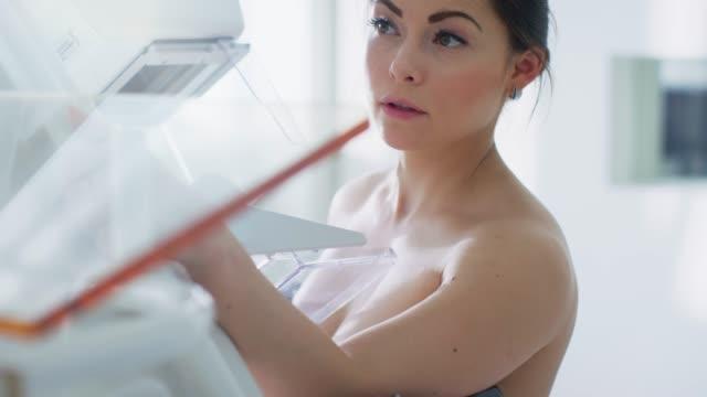 stockvideo's en b-roll-footage met in het ziekenhuis, portret shot van topless vrouwelijke patiënten ondergaan mammogram screening procedure. gezonde jonge vrouw doet kanker preventieve mammografie scan. - breast cancer