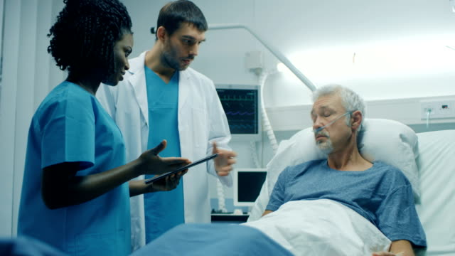 In the Hospital, Senior Man Lying in the Bed, Talks with Doctor and Nurse who Diagnose Him Using Tablet Computer. Technology Helps Cure Patients, Modern Hospital Ward. In the Hospital, Senior Man Lying in the Bed, Talks with Doctor and Nurse who Diagnose Him Using Tablet Computer. Technology Helps Cure Patients, Modern Hospital Ward. Shot on RED EPIC-W 8K Helium Cinema Camera. human resources stock videos & royalty-free footage