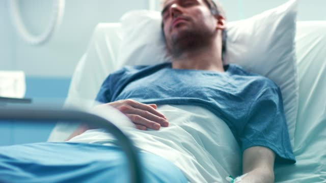 In the Hospital Sick Male Patient Lies on a Bed Sleeping, Heart Rate Monitor On His Finger. Bright and Modern Medical Ward. In the Hospital Sick Male Patient Lies on a Bed Sleeping, Heart Rate Monitor On His Finger. Bright and Modern Medical Ward. Shot on RED EPIC-W 8K Helium Cinema Camera. cancer patient stock videos & royalty-free footage