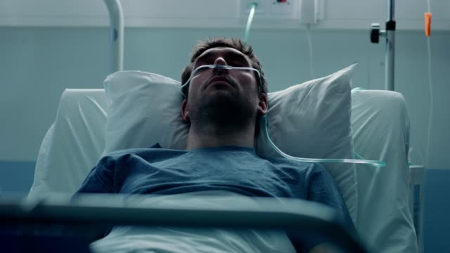 in the hospital sick male patient sleeps on the bed, he's wearing nasal cannula to help him breath. terminally ill man in a come.  sad and blue scene. - morte video stock e b–roll
