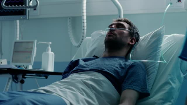 i sjukhuset sjuka manliga patienten sover på sängen, sjuksköterska in medicinska ward kontroller hans vitals och släpp counter. ledsen och blå scen. - intensivvårdsavdelning bildbanksvideor och videomaterial från bakom kulisserna