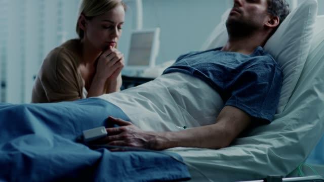 på sjukhuset sjuka man ligger på sängen, hustrun besök förhoppningsvis sitter bredvid honom och ber för hans snabba återhämtning. tragisk, dyster och vemodiga scen. - maka bildbanksvideor och videomaterial från bakom kulisserna