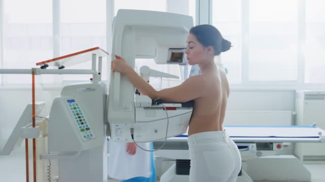 In the Hospital, Side View Shot of Topless Female Patient Undergoing Mammogram Screening Procedure. Healthy Young Female Does Cancer Preventive Mammography Scan. Modern Hospital with High Tech Machines. In the Hospital, Side View Shot of Topless Female Patient Undergoing Mammogram Screening Procedure. Healthy Young Female Does Cancer Preventive Mammography Scan. Modern Hospital with High Tech Machines. Shot on RED EPIC-W 8K Helium Cinema Camera. mammogram stock videos & royalty-free footage